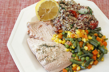 Dinner of tricolor quinoa recipe with mixed vegetables and poached wild salmon with dill and lemon half. Meal of vegetables mix, tricolor quinoa dish and herb salmon