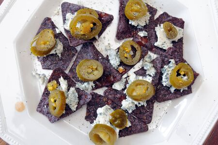 hot sauce: Organic blue corn chips, blue cheese crumbles, jalapeno slices and hot sauce ready to eat as a delicious snack food. Alternative nachos of blue corn chips, blue cheese and jalapeos