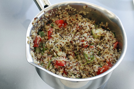 prepared dish: Three different color quinoa seeds after cooked in a pan with sweet red bell pepper, basil, sunflower seeds, and cucumber. Prepared quinoa dish in a stainless steel pan Stock Photo