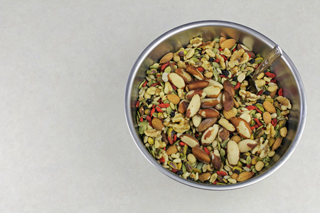 pistachios: Healthy snack variety of dried fruit, seeds and nuts in a stainless steel bowl. Sunflower seeds, pumpkin seeds, pine nuts, almonds, goji, pistachios, and similar mixed