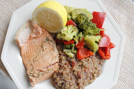 florets: Poached wild salmon with dill herb, tricolor quinoa, lentil and vegetables recipe with green broccoli florets and red sweet bell pepper with a lemon half