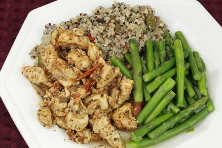 chunk: Delicious dinner of cooked chicken chunks with tomatoes and herbs, asparagus spears with butter and three colors of organic quinoa with vegetables on a white plate.