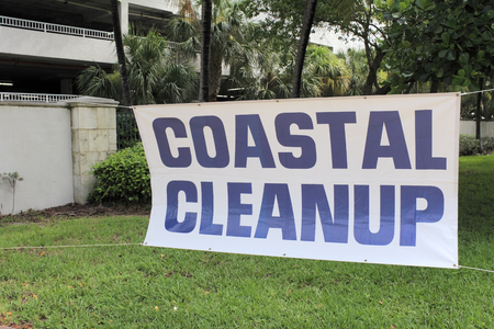 cleanup: Fort Lauderdale, FL, USA - September 20, 2014: Coastal Cleanup sign with blue lettering and a white background. The sign is at the entrance to Earl Lifshey Ocean Park.