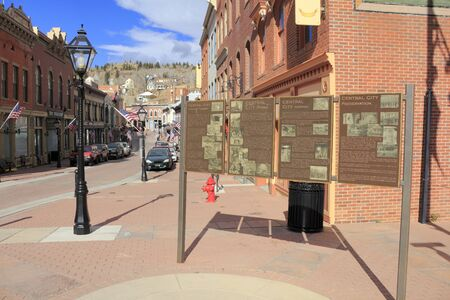 co: Central City, CO, USA - November 7, 2014: Four large historic plaques on a street of antique brick buildings.  Historic downtown street with many old brick buildings with flags Editorial