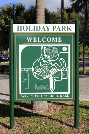 a public notice: Fort Lauderdale, FL, USA - November 30, 2014: Large metal sign welcoming visitors to Holiday Park. The sign   has a map of the park and says the park is closed 11 PM to 5 AM. Editorial