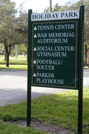a public notice: Fort Lauderdale, FL, USA - November 30, 2014: A sign listing park areas with arrows pointing the way. Five areas of the park listed on a sign and symbols directing the way