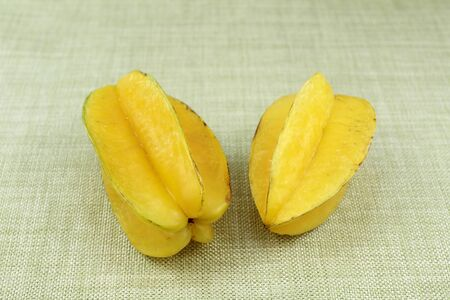 placemat: A couple of yellow carambola fruits on a green cloth placemat. This pair of raw and ripe yellow tropical fruit has the shape of a five pointed star and is sweet and mildly sour. Stock Photo