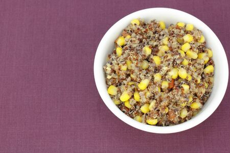 red cooked: Mix of organic red quinoa cooked with yellow corn and red tomato in a white bowl on a purple cloth placemat. Vegetarian recipe of red quinoa, corn and diced tomatoes. Stock Photo