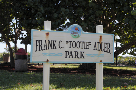 larger: Dania Beach, FL, USA - December 7, 2014: Entry sign to Frank C Tootie Adler Park near the entrance to a larger park. Small park sign located in a larger park