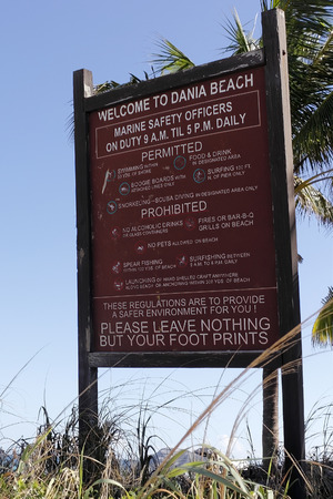 directives: Dania Beach, FL, USA - December 7, 2014: Large painted wooden sign welcoming and informing visitors about the regulations of permitted and prohibited activities. Editorial