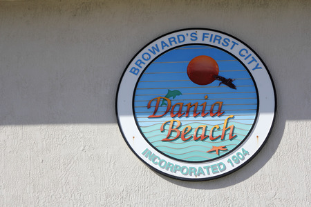 incorporated: Dania Beach, FL, USA - December 7, 2014: A colorful round sign on a building that says, Broward s First City Dania Beach, Incorporated 1904. A Dania Beach sign.