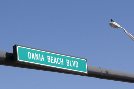 street sign: White and green Dania Beach Blvd in Dania Beach, Florida street sign with a bright blue sky in the background. Dania Bach Blvd street sign on a sunny day