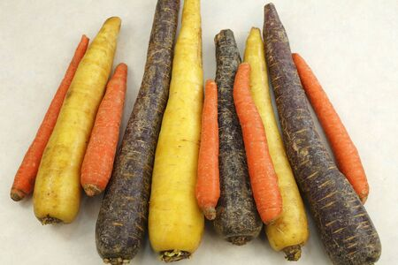 kitchen counter top: Ingredient mix of whole, raw orange, yellow and purple carrots on a beige countertop.  Three different colors of organic whole raw carrots on a kitchen counter top