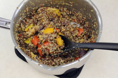 red cooked: Red black and white organic quinoa cooked with purple onions, yellow orange red sweet bell peppers and chicken. Prepared chicken vegetables with quinoa in a pan.