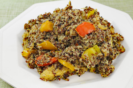 tricolor: One white plate with cooked tricolor organic quinoa grain seed and a colorful mixture of red yellow and orange sweet bell peppers with purple onion for supper Stock Photo