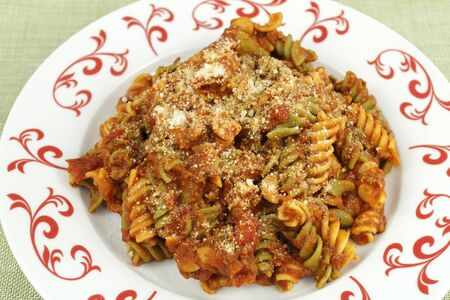 tri  color: Semolina rotini spiral pasta made with vegetables of spinach, tomatoes and carrots. Closeup pasta dish served with chunky tomato pasta sauce on a red and white plate. Stock Photo