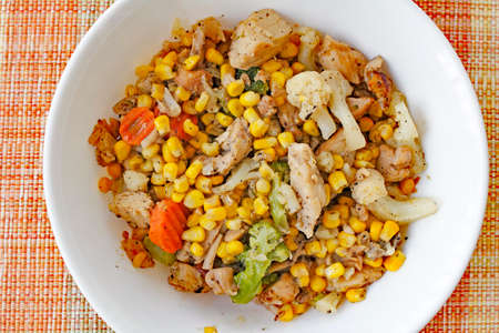 corn meal: Cooked meal of chicken, carrots, broccoli, cauliflower and corn with pepper served in a round white bowl on a colorful placemat. Chicken and mixed vegetables supper.