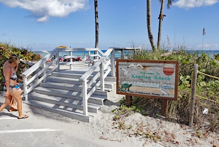 fl: Hollywood, FL, USA - December 7, 2014: Welcome to Keating Beach sign with people walking up to the entrance stairs. People walking to and enjoying sunny Keating Beach. Editorial