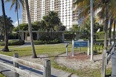 multifamily: Hollywood, FL, USA - December 14, 2014: Small Harry Berry Park and sign with some sitting areas and restrooms. A tall multi-family building rises up behind Harry Berry Park. Editorial