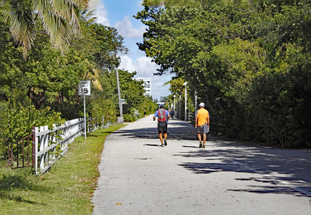 fl: Hollywood, FL, USA - December 7, 2014: People walk, jog and bike along the popular fitness trail near  Hollywood beach on a sunny day. Many people exercise on a walkway. Editorial