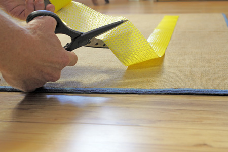 non skid: Male caucasian hands with black handle stainless steel scissors cutting to size a strip of yellow anti-slip rug grip tape. Cutting and placing anti-skid carpet tape.