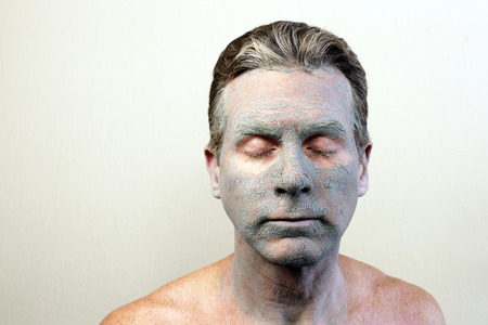clays: Adult caucasian male with eyes closed wearing a drying green bentonite clay facial mask. Front of white guy with a cracking and almost dry face beauty mask of bentonite clay. Stock Photo