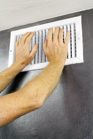 Twee volwassen handen geplaatst over een out ontluchter register van een cv-installatie op een grijze muur in de buurt van een wit plafond. Een witte metalen ontluchter met twee volwassen mannelijke blanke handen op