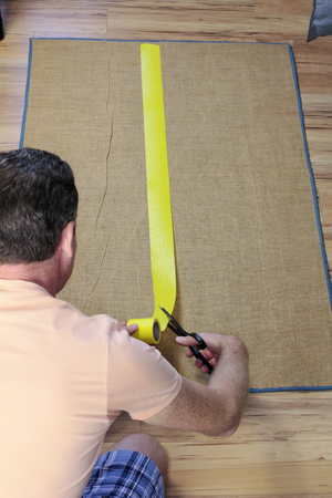 non skid: Adult male placing and cutting a strip of tape that helps prevent a floor rug from slipping. Putting some anti-slip rug tape on a back of a rug for accident prevention.