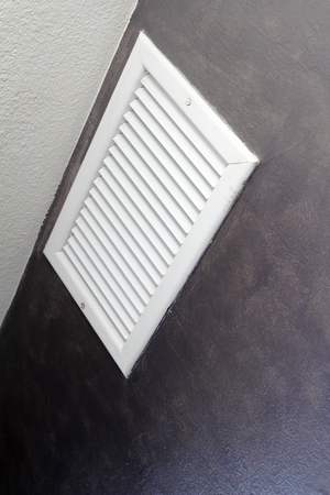 outflow: White metal air vent seen at an angle near a white ceiling on a gray interior wall of a home. Medium sized outflow air register high on a living room wall of a residence.