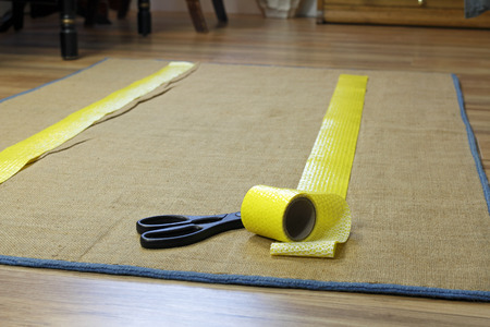 non skid: Anti-slip double sided adhesive texture tape with removable yellow plastic on one side. A roll of tape near scissors is placed on the floor rugs backing in two strips.