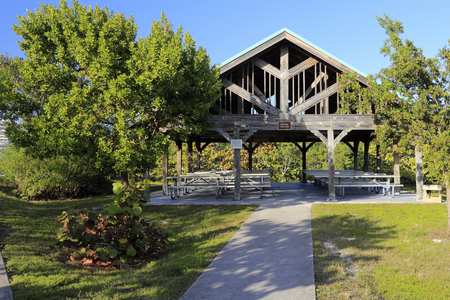 fl: Hollywood, FL, USA - December 20, 2014: Weathered wooden pavilion covered with open sides and picnic tables in John U Lloyd Beach State Park near Port Everglades.This nice eating area in John U Lloyd Beach State Park near Port Everglades is open on the si
