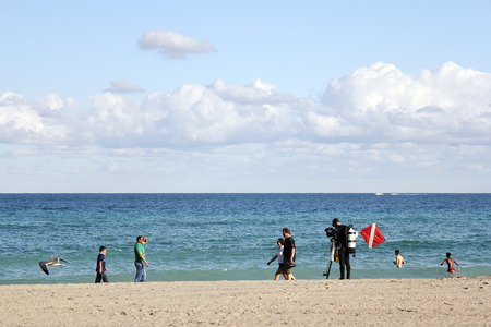 fl: Hollywood, FL, USA - December 14, 2014: A diver in a full wet suit with an oxygen tank on his back and a flag to one side examines some of his equipment as people walk by. Editorial