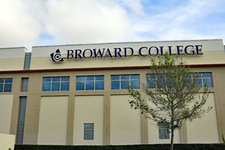campus building: Coconut Creek, FL, USA - January 3, 2015: Exterior of Broward Community College North Campus building and sign with a tree in front and a blue sky with white clouds. Editorial