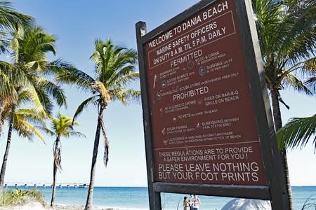 fl: Dania Beach, FL, USA - December 7, 2014: Tropical welcome sign to Dania Beach, Florida on a blue sky sunny day. Atlantic coast beach entrance with trees and people. Editorial