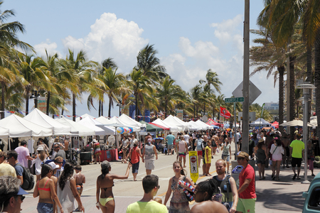 mucha gente: Fort Lauderdale, FL, EE.UU. - 23 de mayo, 2015: La gente leer detenidamente los vendedores dosel cubierto en la Gran Fiesta Americana Beach. Las personas se divierten en una fiesta en la playa en la A1A.