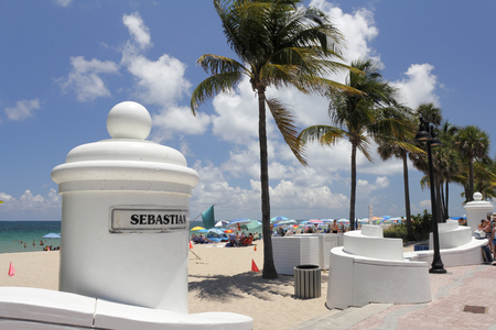 fort lauderdale: Fort Lauderdale, FL, USA - May 23, 2015: White pillar wall sign to Sebastian Street and SR A1A beach. People on the sunny beach at the end of Sebastian Street.