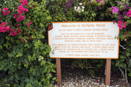 fl: Coconut Creek, FL, USA - July 21, 2015: Welcome to Butterfly World sign located in Tradewinds Park. A Welcome to Butterfly World sign with flowering plants.