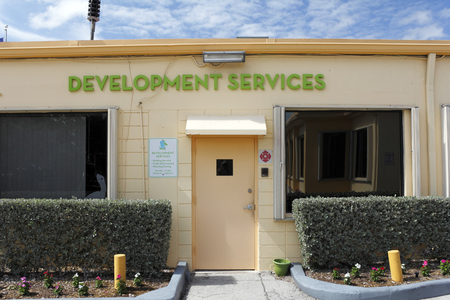 fl: Lauderdale-by-the-Sea, FL, USA - May 16, 2015: Development Services building exterior front entrance. Development Services signs and office entrance on a sunny day. Development services is where they handle building permits, code enforcement and planning