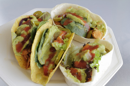 lettuces: One plate full of two hard and two soft shell chicken tacos with vegetables. Hot sauces, lettuces, jalapeno slices and avocado top these chicken tacos on a plate outside.