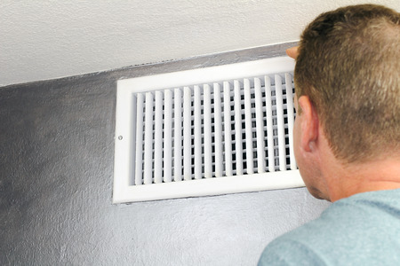 air duct: Mature male peering inside an upper wall white grid air duct on a silver wall near a white ceiling. A guy inspecting a heating and cooling air register duct for maintenance.