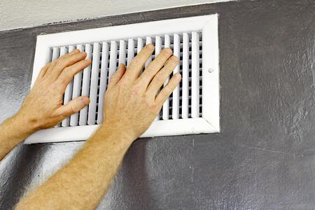 Un paio di mani maschi adulti sentire il flusso d'aria che esce da uno sfiato su un muro vicino soffitto. L'uomo con le mani di fronte a una presa d'aria sensibilità per il flusso d'aria. Archivio Fotografico