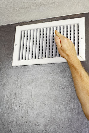 adult wall: One hand of an adult male raised in front of an upper wall air vent checking for air flow. A man holding a hand up in front of an air vent checking the air temperature.