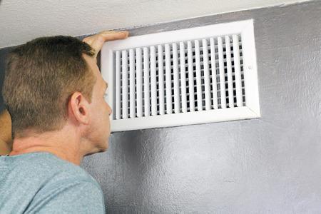 Hombre maduro examen de una rejilla de ventilación de aire de salida y el conducto para ver si necesita limpieza. Un hombre que busca en un conducto de aire principal para ver lo limpio y saludable que es.