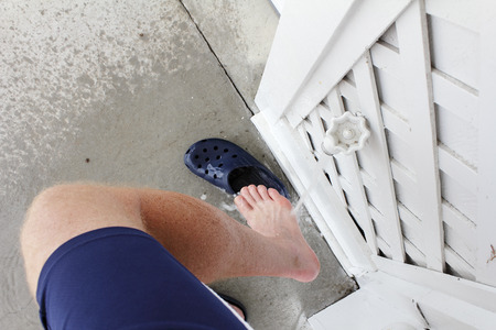 spigot: Right leg of a mature male wearing blue sports shorts rinsing sand from his foot after visiting the beach. Outdoor water spigot spraying sand off a man�s right foot outdoors