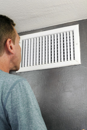 understand: Male examines an indoor air duct register for dirt to understand if he should get it cleaned. One guy in his forties peers into and inspects a furnace central heating vent.