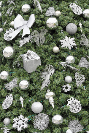 fake christmas tree: Various silver and glitter ornaments on an artificial green Christmas tree closeup. Green Christmas tree with silver and glitter ornaments background. Stock Photo