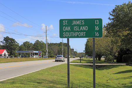 se: Supply, NC, USA - September 29, 2015: Road sign along 211 or Southport Supply Rd SE east towards St. James, Oak Island and Southport. Road sign in Supply, NC. Editorial