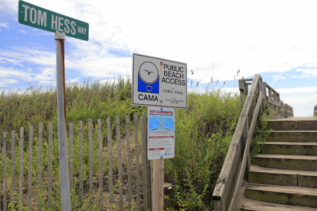 currents: Caswell Beach, NC, USA - September 27, 2015: Public Beach Access, Rip Currents warning and Tom Hess Way signs at an entrance to the beach. Stairs entry to a sunny beach.