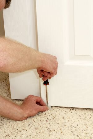 closet door: Caucasian male using a screwdriver to screw in a bypass door guide at the bottom middle carpeted floor of a home closet door. Installing a white plastic door guide. Stock Photo