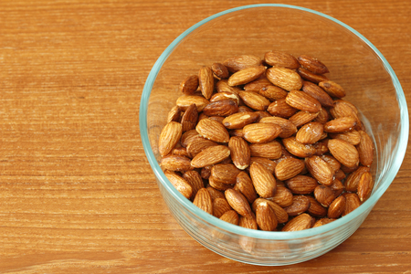 maples: Baked maple syrup coated almonds with salt in a round glass bowl on a wooden table. A healthy and sweet snack of maple syrup coated dry almonds with salt in a bowl.